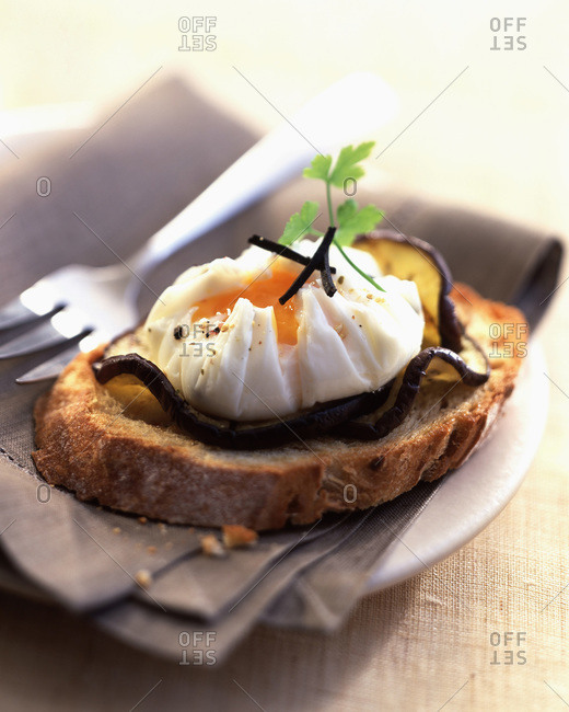 Poached egg with truffles on eggplant and toast