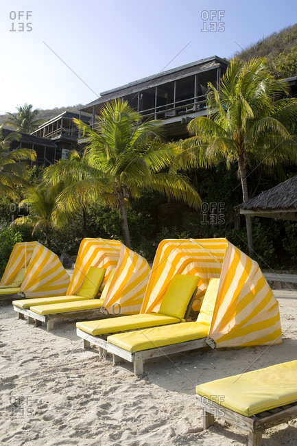Breathtaking view of luxurious beachfront villas and sandy beach with yellow deck chairs with shade.