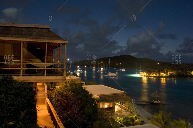 Night view of beachfront cottages and tranquil yachting location.