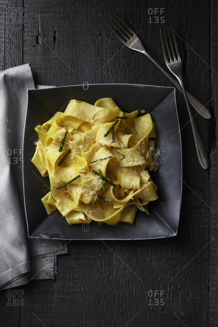 Pappardelle in saffron cream topped with lemon zest, chopped chives and parmesan cheese