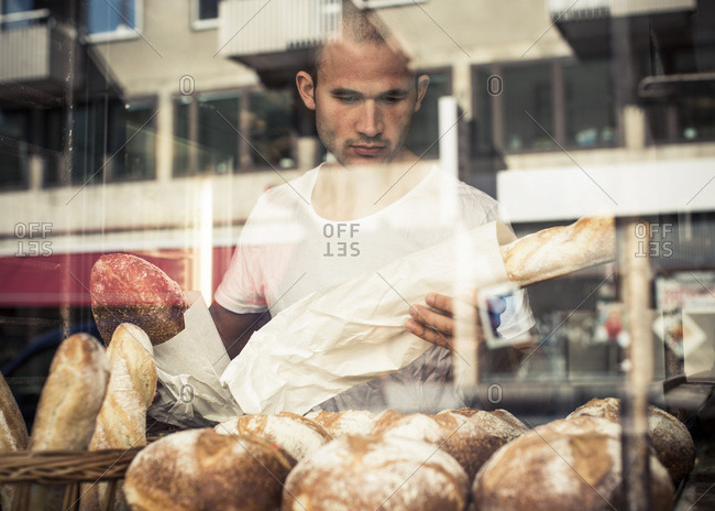 View of  male owner working at bakery through display cabinet