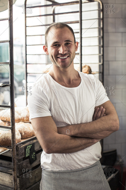 Portrait of confident male owner standing arms crossed in bakery