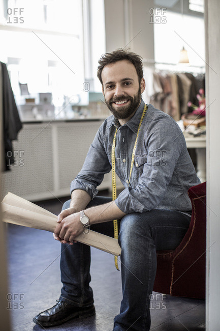 Portrait of confident happy male fashion designer sitting in studio