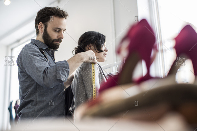 Side view of  male fashion designer measuring woman's shoulder at studio