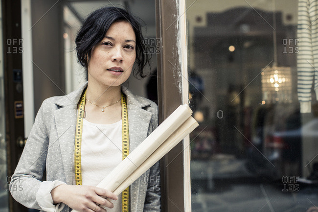 Portrait of female fashion designer holding blueprint while standing outside studio