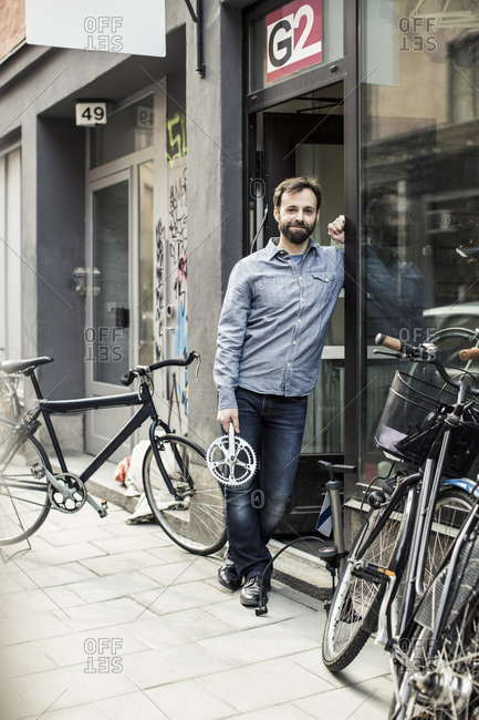 Portrait of  male owner with pedal standing at the doorway of bicycle repair shop