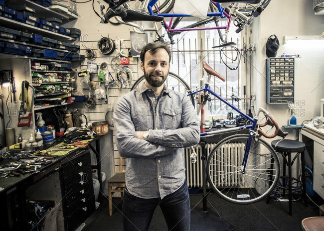 Portrait of  male owner standing arms crossed at bicycle repair shop