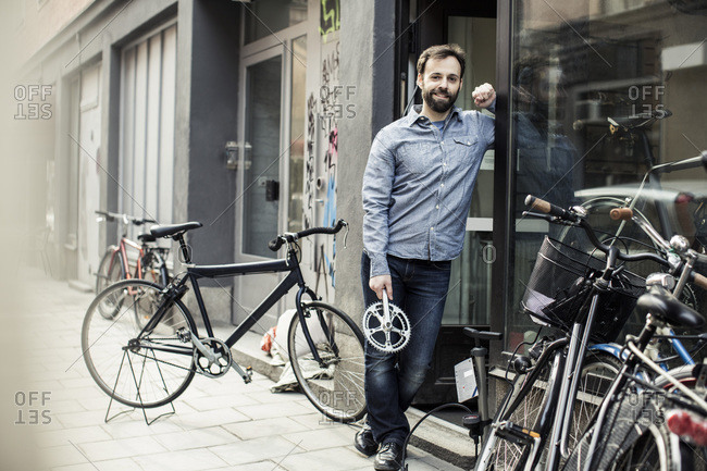 Portrait of confident  male owner with pedal standing at the entrance of bicycle repair shop