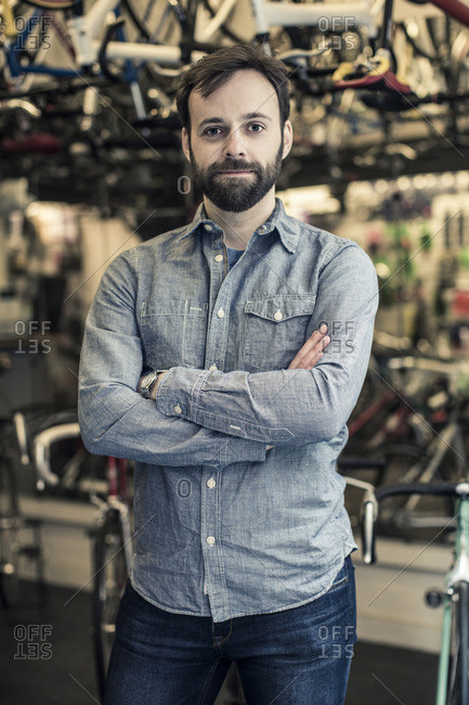 Portrait of confident  male owner standing arms crossed at bicycle repair shop