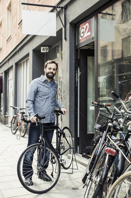Portrait of happy  male owner standing outside bicycle repair shop