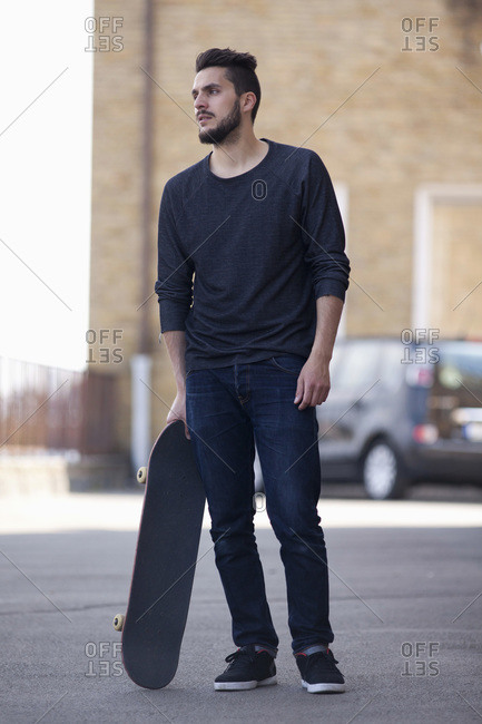 Full length of young man looking away while standing with skateboard on street