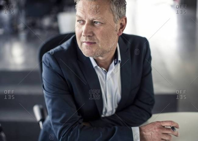 Businessman looking away while sitting at desk in office