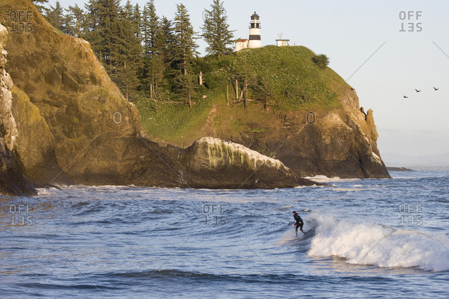 USA, Washington, Cape Disappointment Lighthouse. Male surfer.
