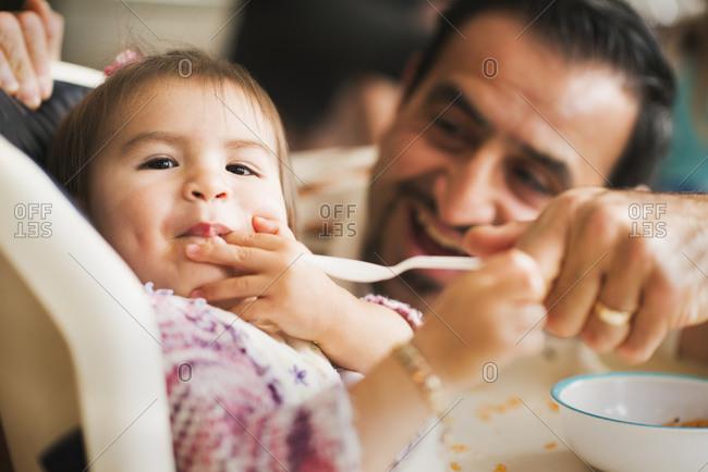 Hispanic father feeding daughter in high chair
