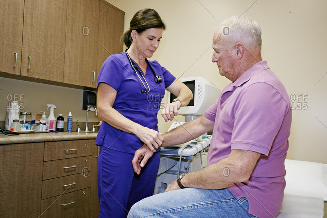 Nurse checking patient's pulse in office
