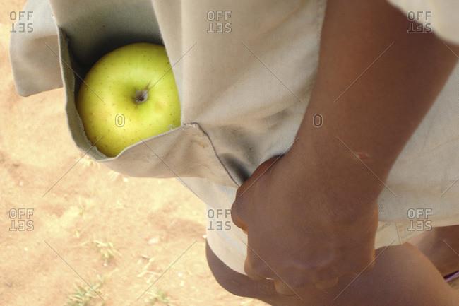 Benin, Porto-Novo. Green apple hidden in the pocket of a boy wearing a beige school uniform