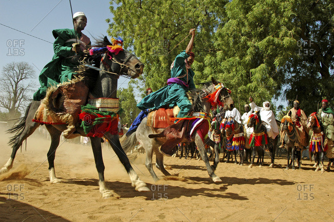Cameroon, Pouss. African horsemen riding a horse racing on a dusty trail in front of a group of other horsemen