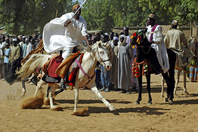 Cameroon, Pouss. African horsemen riding a horse racing on a dusty trail