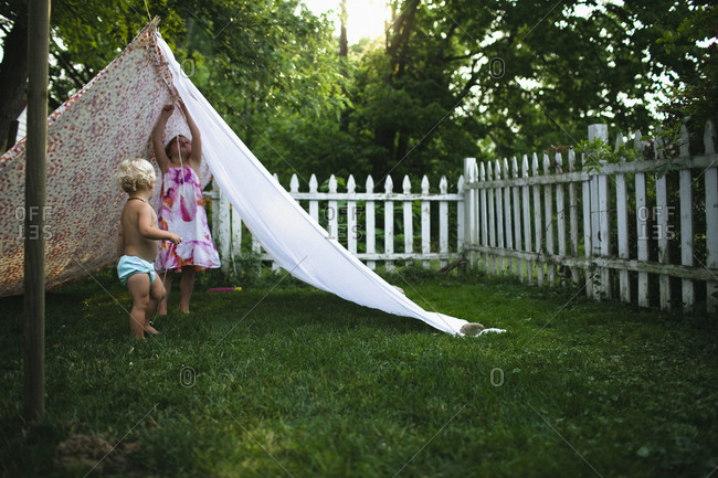 Two children make a tent out of sheets