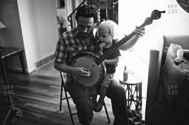 A man holds a child while playing the banjo