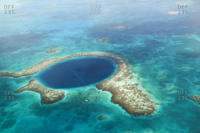 aerial view of Blue Hole, sailboat anchored nearby, Lighthouse Atoll, Belize