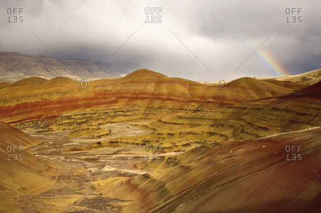 USA, Oregon, John Day Fossil Beds National Monument. Detail of Painted Hills and partial rainbow in storm clouds.