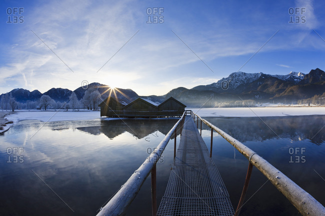 Germany, Bavaria, Kochelsee, View of pier and huts beides lake with mountains in Bavarian foothills of alps
