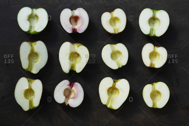 Cored apple rows on black surface