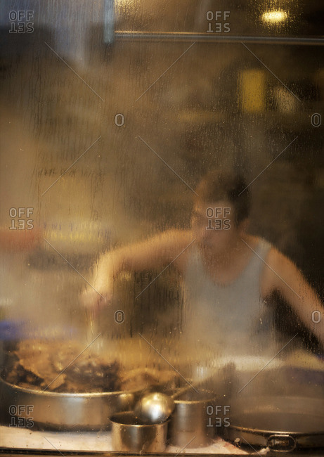 A cook preparing meals by a display window in Kowloon, Hong Kong