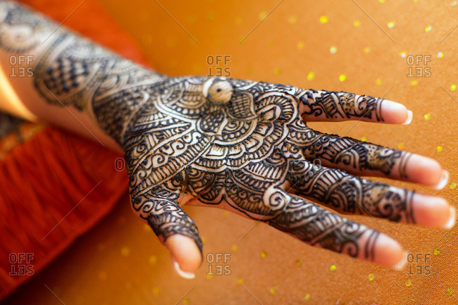 Close up of hand with intricate henna design