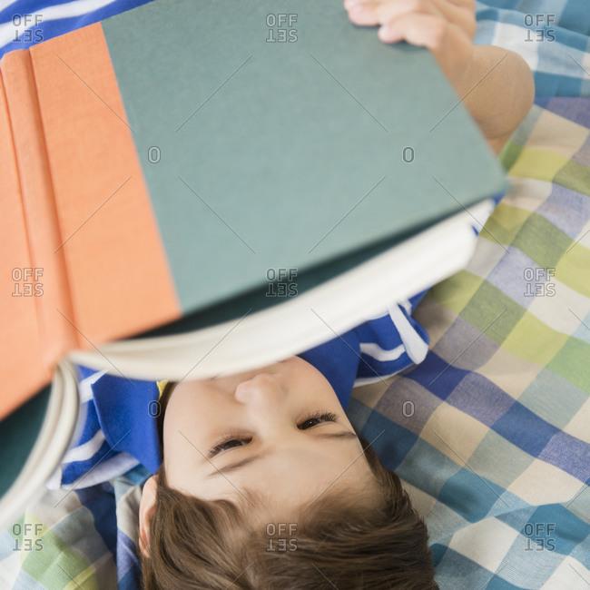 Hispanic boy reading on bed