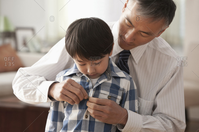 Father buttoning son's shirt