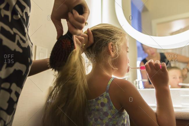 Caucasian mother brushing daughter's hair