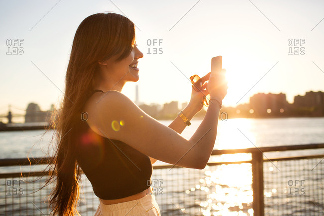 A woman takes a photo with her smartphone