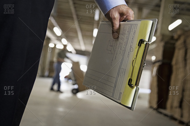 Close up of man holding clipboard in warehouse