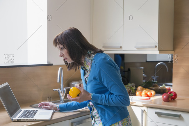 Mature woman using laptop while cooking