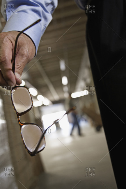 Close up of man holding eyeglasses in warehouse