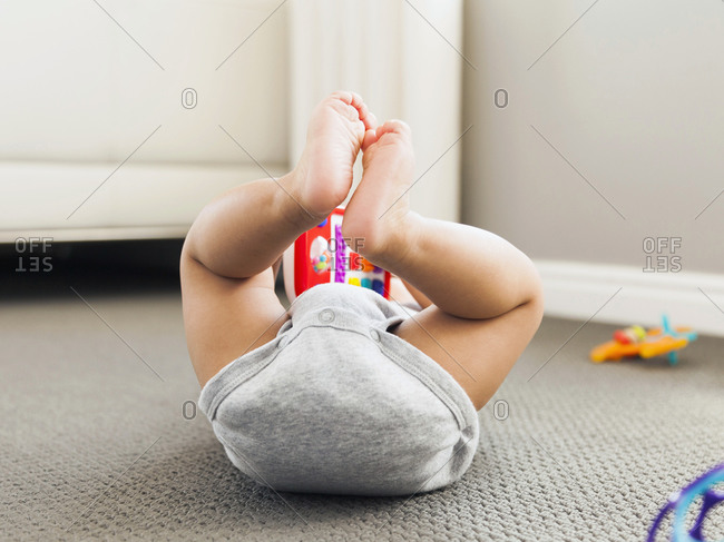 Baby boy (2-5 months) lying on floor playing