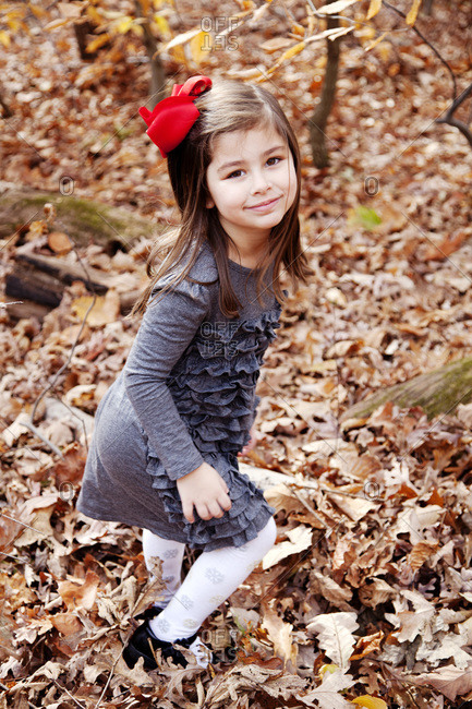 Young girl plays in a pile of leaves