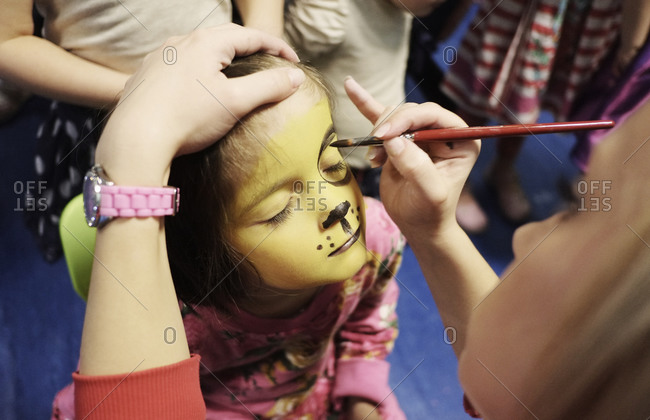 A four-year-old girl at a face-painting party.