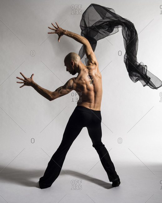 Latin looking male dancer, in a jazz pose shot from the back
