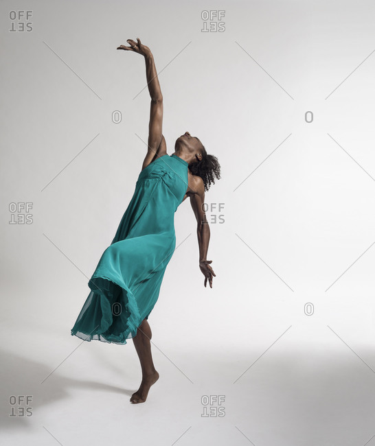 Afro-african female dancer in a green dress against white background