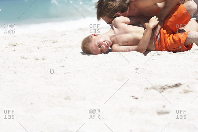 Father and son playing on sandy beach, laughing, side view