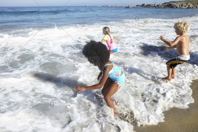 Three children playing in surf on beach, rear view, sea in background