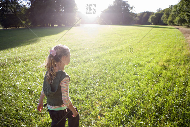 Blonde girl  walking in field in bright sunlight, rear view, trees in background (lens flare)