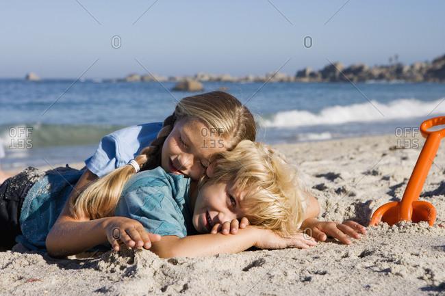 Boy and girl lying on sandy beach beside orange spade, smiling, side view