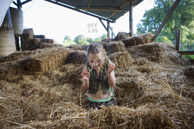 Girl playing amongst hay in barn, smiling, front view