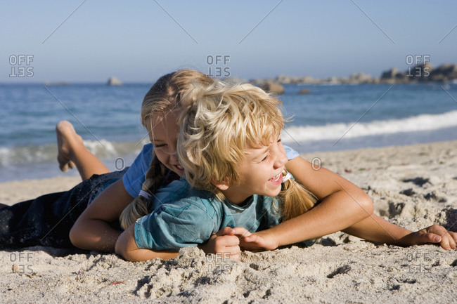 Boy and girl playing on sandy beach, smiling, side view