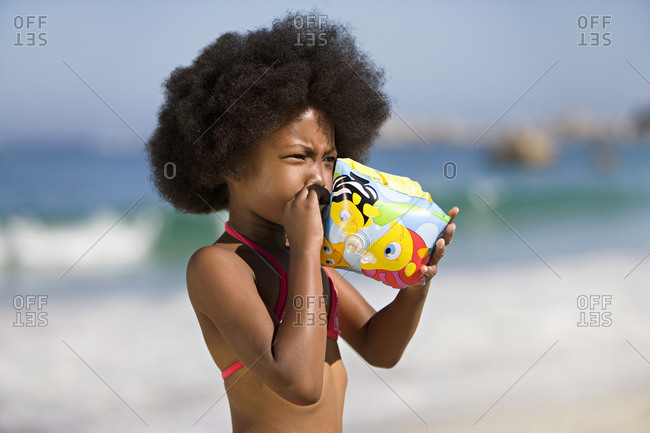 Girl blowing air into inflatable armband, standing on sandy beach, side view