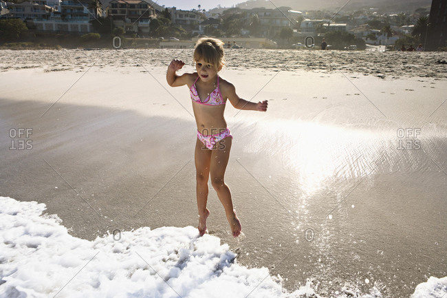 South Africa, Cape Town, girl playing in surf at beach, resort in background